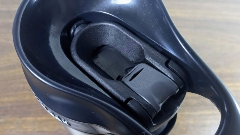 The arms in the open position, with the lock button in place to keep it from closing the spout